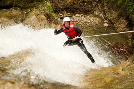 rappel: adult man wearing waterproof equipment descending a waterfall Stock Photo