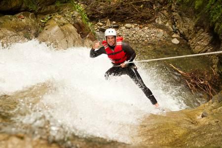 descending: adult man wearing waterproof equipment descending a waterfall Stock Photo