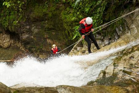 rappel: team of two young womens wearing waterproof equipment descending a waterfall Stock Photo