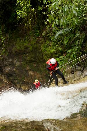 team of two young womens wearing waterproof equipment descending a waterfall photo