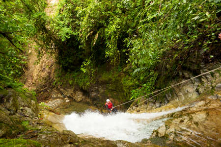 adult woman wearing waterproof equipment descending a waterfall photo