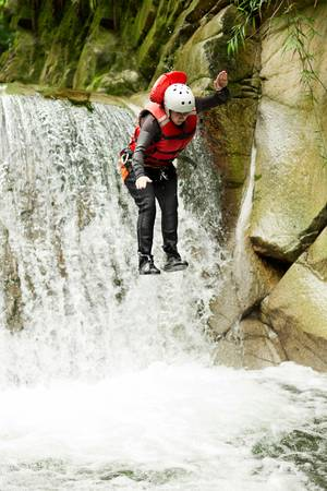 well equipped: well equipped woman jumping into a natural pool during a canyoning expedition