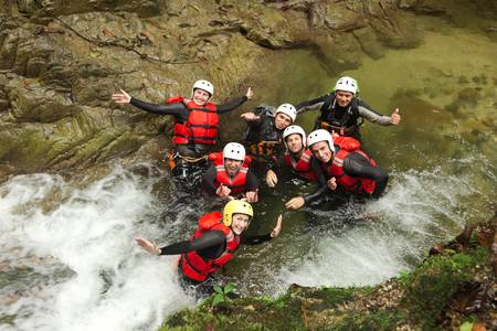 extreme danger: group of active young people during a canyoning expedition in ecuadorian rainforest