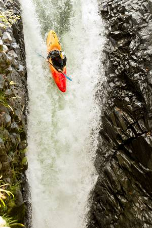 man waterfalls: courageous kayaker in a vertical diving position