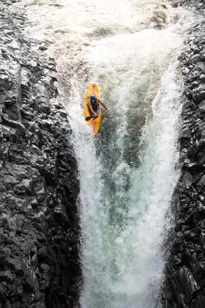 adventure sports: courageous kayaker in a vertical diving position