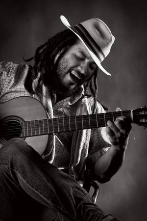 rastafarian man playing classic guitar photo