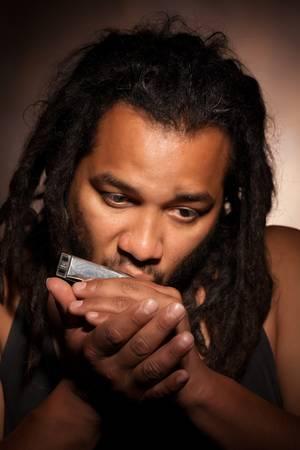 rastafarian man playing mouth harmonica