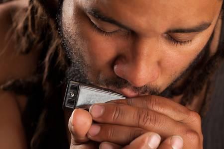 rastafarian man playing mouth harmonica Stock Photo - 18340462