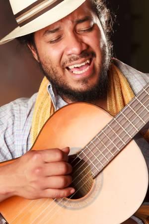 south american: rastafarian man playing classic guitar Stock Photo