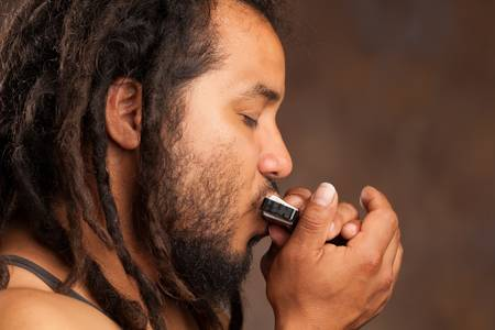 Rastafarian man playing mouth harmonica photo