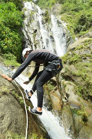 Canyoning guide trying out a new route in Chama waterfall, Banos De Agua Santa, Ecuador photo