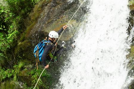 Waterfall descent by a professional canyoning istructor. Stock Photo