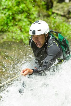 rappel: canyoning guide trying out a new route in chama waterfall, banos de agua santa, ecuador Stock Photo