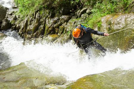 rappel: Canyoning guide trying out a new route in Chama waterfall, Banos De Agua Santa, Ecuador