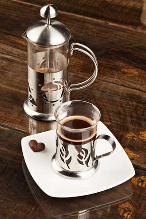 water drip: elegant coffee cup served along with filter against heavy polished wooden table
