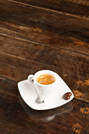 espresso cup: small espresso cup and chocolate heart, against polished table top
