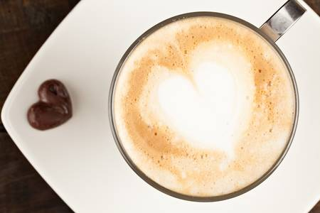 creamer: beautifuly decorated cup of cappucino and chocolate heart, against polished table top