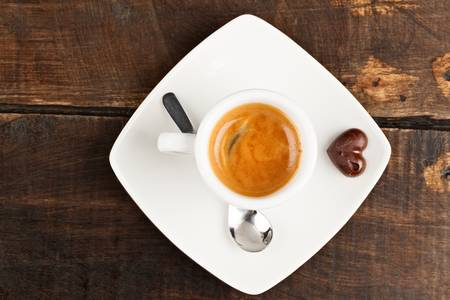 crema: small espresso cup and chocolate heart, against polished table top
