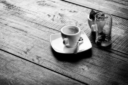 unmarried: espresso empty cup on wooden table top, monochrome image.
