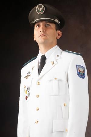 ecuadorian police official dressed up in formal uniform, studio shot. photo