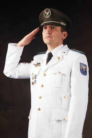 ecuadorian police official dressed up in formal uniform saluting, studio shot. photo