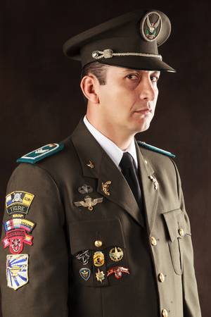 highly decorated ecuadorian police official dressed up in formal uniform, studio shot. photo