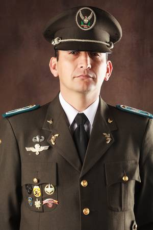 sergeant: highly decorated ecuadorian police official dressed up in formal uniform, studio shot.