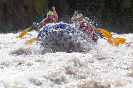 A group of men and women, with a guide, white water rafting on the Patate river, Ecuador photo