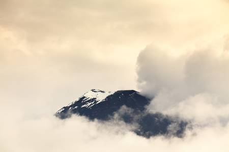 tungurahua: discrete view of the tungurahua volcano on through the clouds,