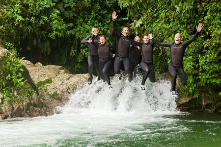senior group: group of six people, three pairs jumping in the same time into a waterfall, canyoning expedition.