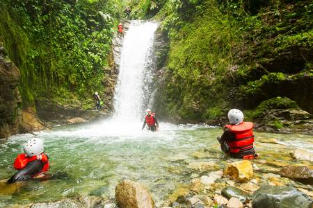 Couple of tourist admiring the natural beauty of a waterfall, canyoning trip.