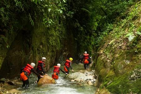 group of people crawling into canyons of llanganates nation park in ecuador. Фото со стока