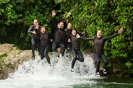 Group of six people, three pairs jumping in the same time into a waterfall, canyoning expedition. photo