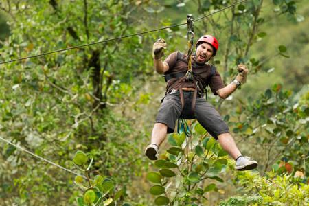 adult man, zip line adventure in ecuadorian rainforest.