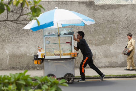 Ambato,Ecuador - January 24,2012: Child labor still not abolished in 3rd world countries, it is not a genaral practice but still, some poor families forces their childrens to work, as you can see this boy seling popcorn on the streets of Ambato,Ecuador -