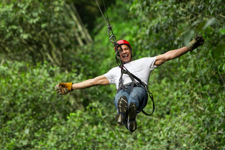 adult man on zip line, ecuadorian andes