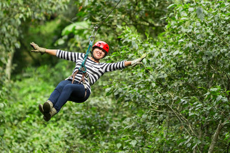 adult woman on zip line, ecuadorian andes