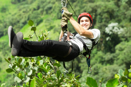 adult man on zip line, andes rain forest in ecuador Stockfoto