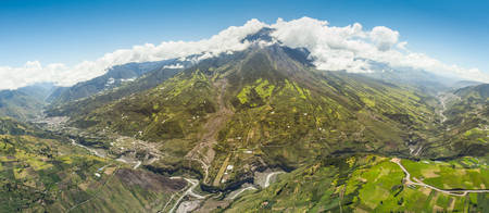 strombolian: tungurahua volcano panoramic aerial shot, city of banos de agua santa on the left side, pastaza river and popular sightseeing in the foreground, full zise helicopter high altitude,