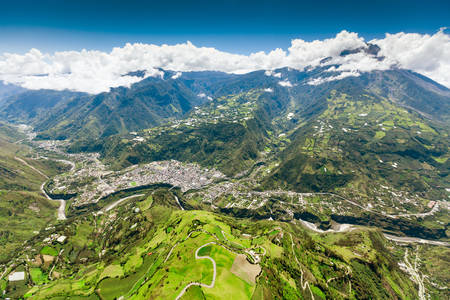 tungurahua: aerial shot of banos de agua santa,nne to sww, tungurahua volcano in the background and pastaza river in foreground