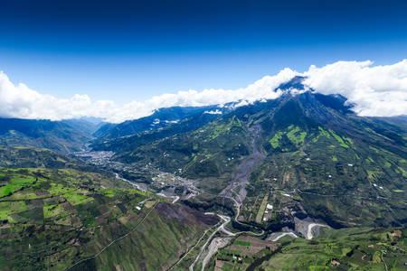 strombolian: tungurahua volcano high altitude aerial wide shot, city of banos de agua santa on the far left, visible crater