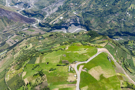 top angle view: high altitude aerial shot over farmland in tungurahua province, ecuador. pastaza river in the background,