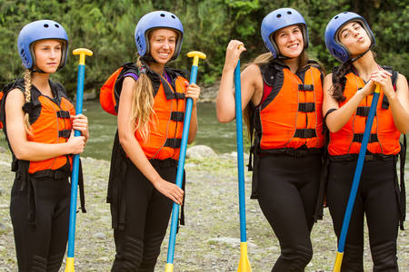 lifejacket: group of four young ladies prepared to go white water rafting, wearing specific equipment