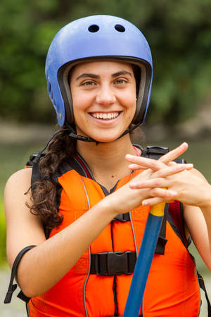 lifejacket: portrait of smiling young lady wearing white water rafting equipment, looking straight into the camera Stock Photo