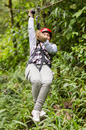 gliding: adult tourist wearing casul clothing on zip line trip, tungurahua province , ecuador Stock Photo