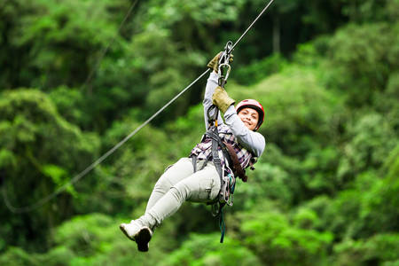 wire: adult tourist wearing casul clothing on zip line trip, selective focus against blured forest Stock Photo