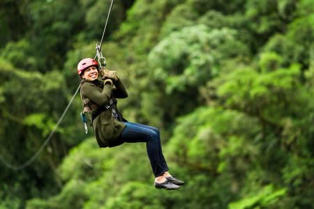 adult slime afro woman on zipline in ecuadorian rainforest, nearby banos de agua santa Standard-Bild