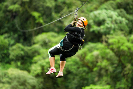 oversized adult woman on zip line trip,selective focus against blured rain forest
