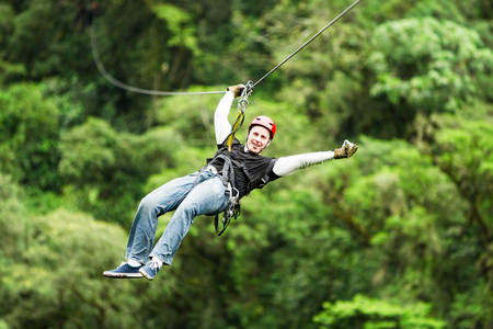 flight helmet: adult male tourist wearing casul clothing on zip line or canopy experience in ecuadorian rain forest