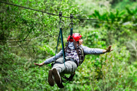 adult tourist wearing casul clothing on zip line trip, selective focus against blured forest Archivio Fotografico